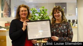 Kristina Bergman Alme (L) och Marina Johansson (S) visar upp dokumentet som visar att Göteborg lovat jobba med utbildning och livslångt lärande inom ramen för det sociala protokollet.
