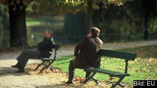 En man sitter på en bänk.
