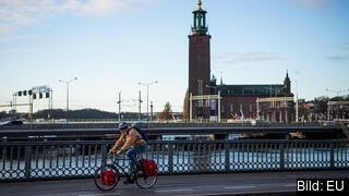 En man på en cykel framför Stockholm stadshus