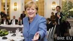 Tysklands förbundskansler Angela Merkel sträcker ut en hand till Frankrikes president Emmanuel Macron.